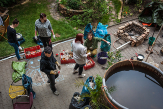 """At Suzie's home, residents of the community participate in spring cleaning in front of the """"hippy jacuzzi""""."""