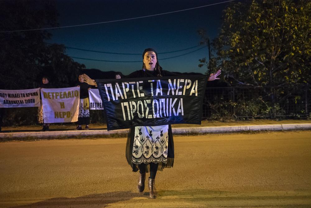 Una donna durante una protesta nell'Epiro. Sullo striscione: VIENI A PRENDERTI L'ACQUA.