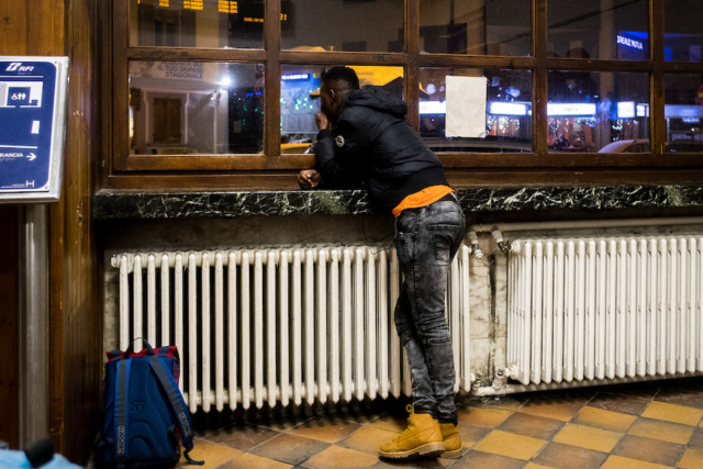 A refugee in Bardonecchia station. Volunteers will provide shoes and warm clothes
