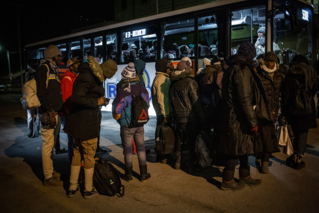 Refugees board the coach which will take them to the last town before the French border.
