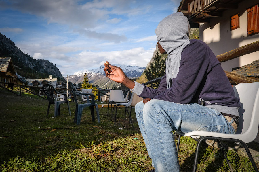 In Claviere, a refugee looks at the mountains while waiting for the time to depart.