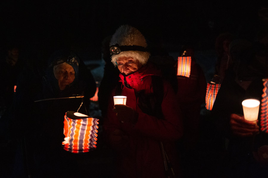 A volunteer holds a lantern at the outreach run.