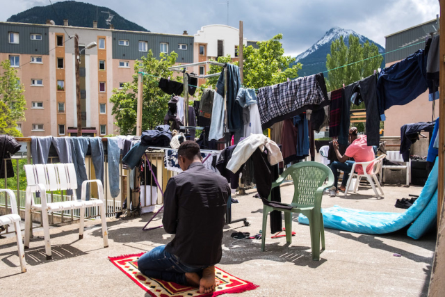 A refugee prays on the terrace of the Refuge Solidaire in Briançon.