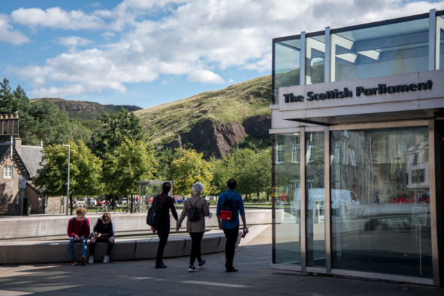 People walking by the Scottish Parliament building in Edinburgh.