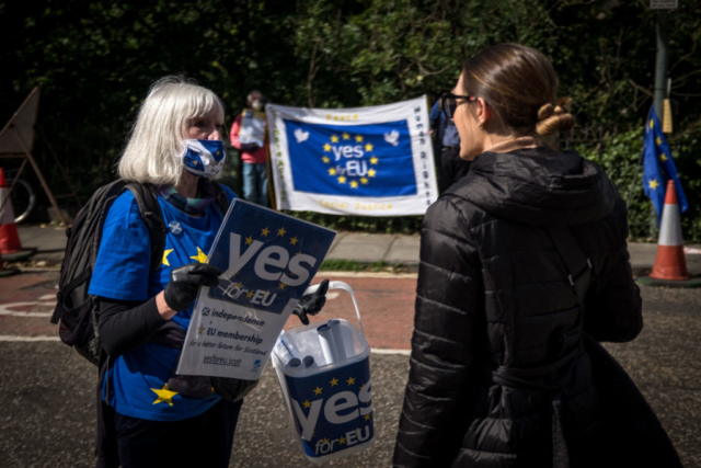 An activist with YES for EU discusses independence and rejoining the EU with a pedestrian.