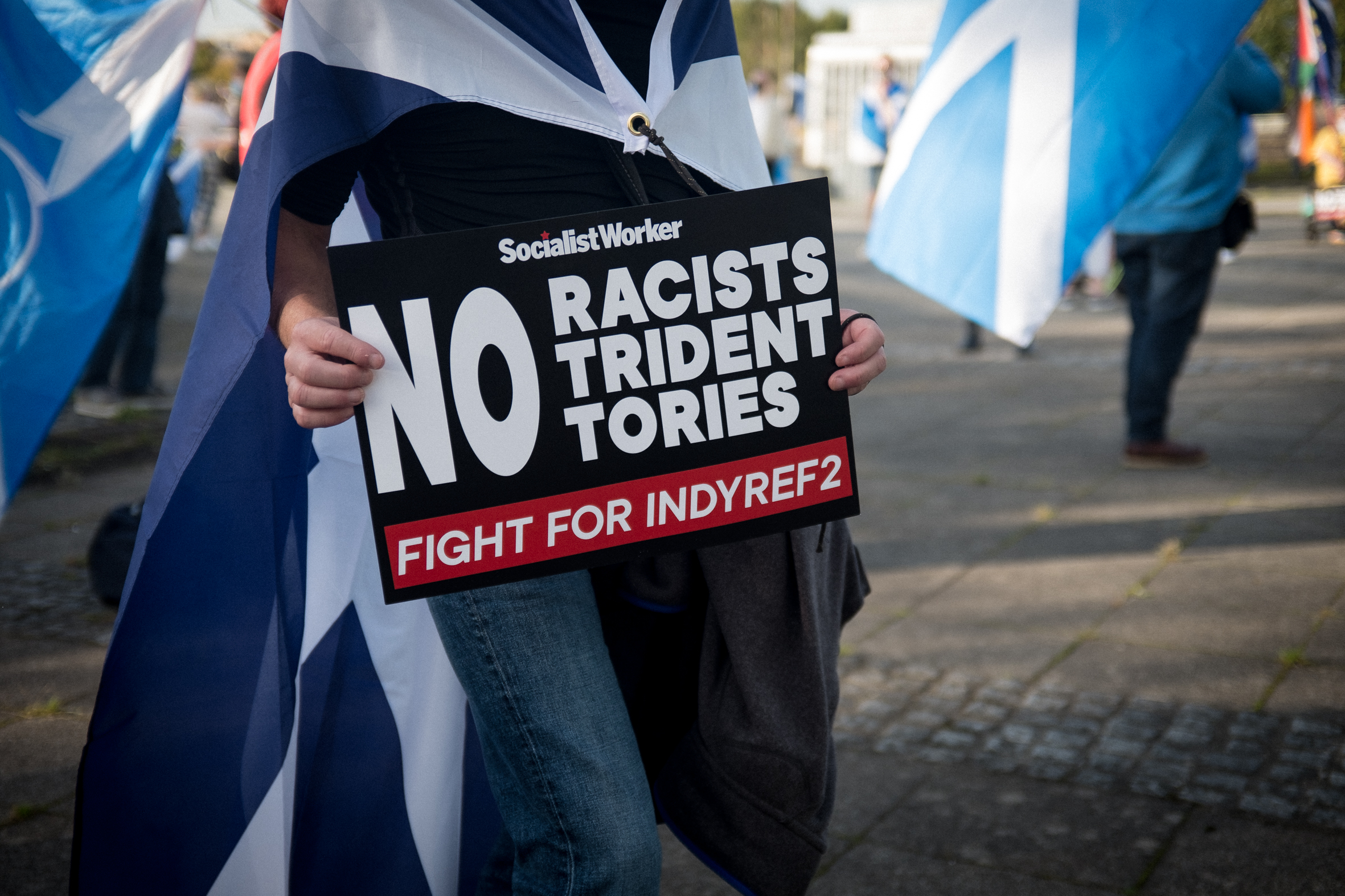 An All Under One Banner protester holds a sign condemning racism, the British nuclear program and the Conservative party.