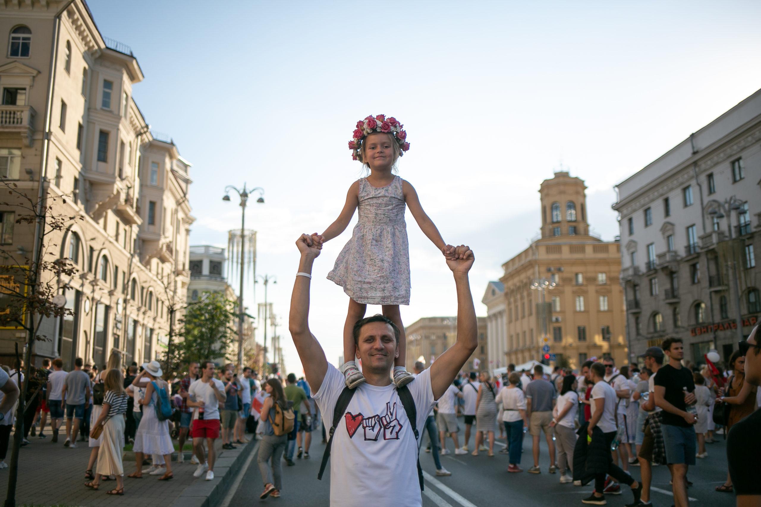 Ein Mann mit seiner Tochter auf der Praspiekt Niazaliežnasci, der Hauptstraße von Minsk. August 2020.