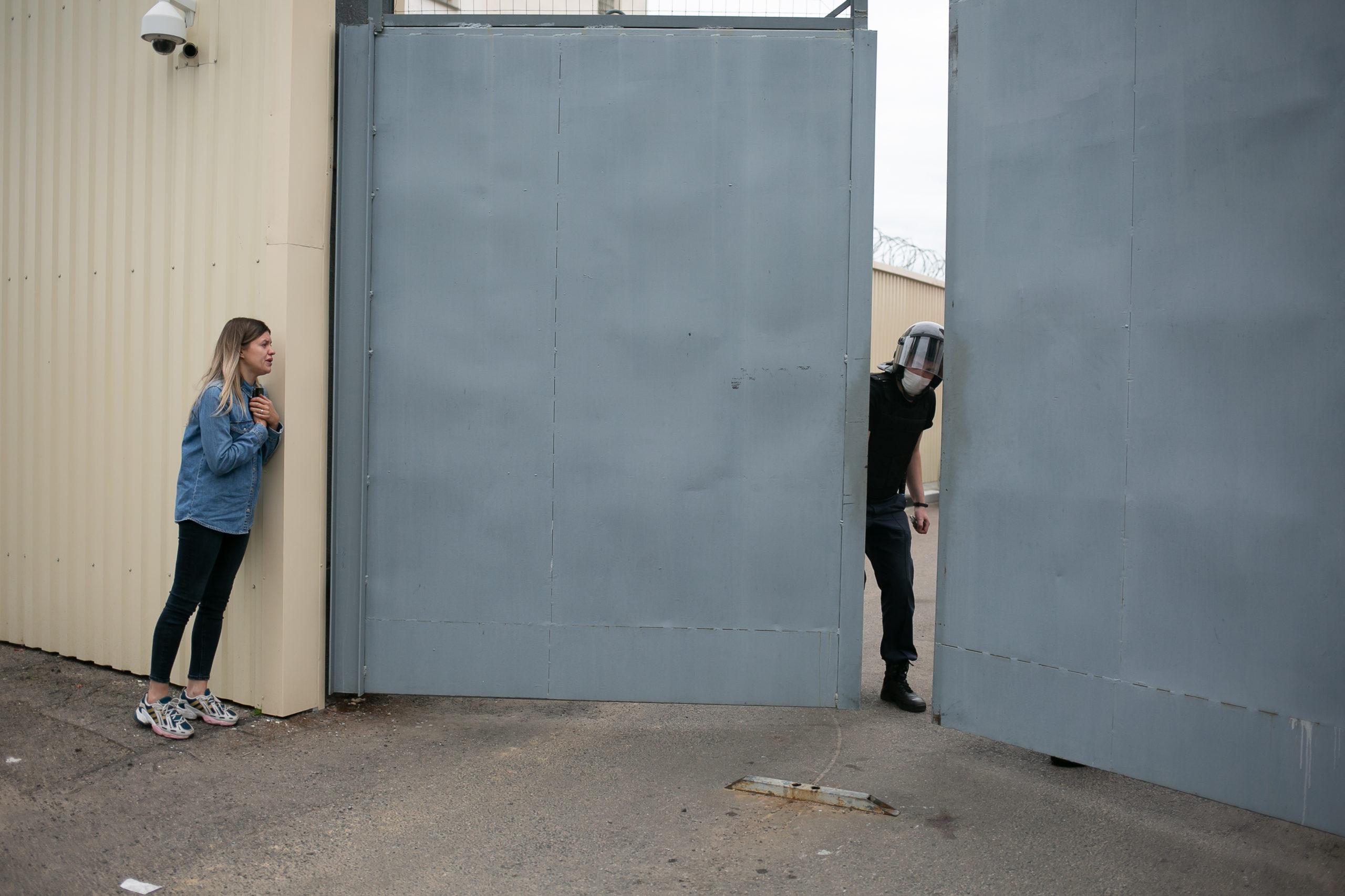 Eine junge Frau spricht mit einem Polizisten, als er die Tore des Gefängnisses in der Akrestsin-Straße schließt. Minsk, August 2020.