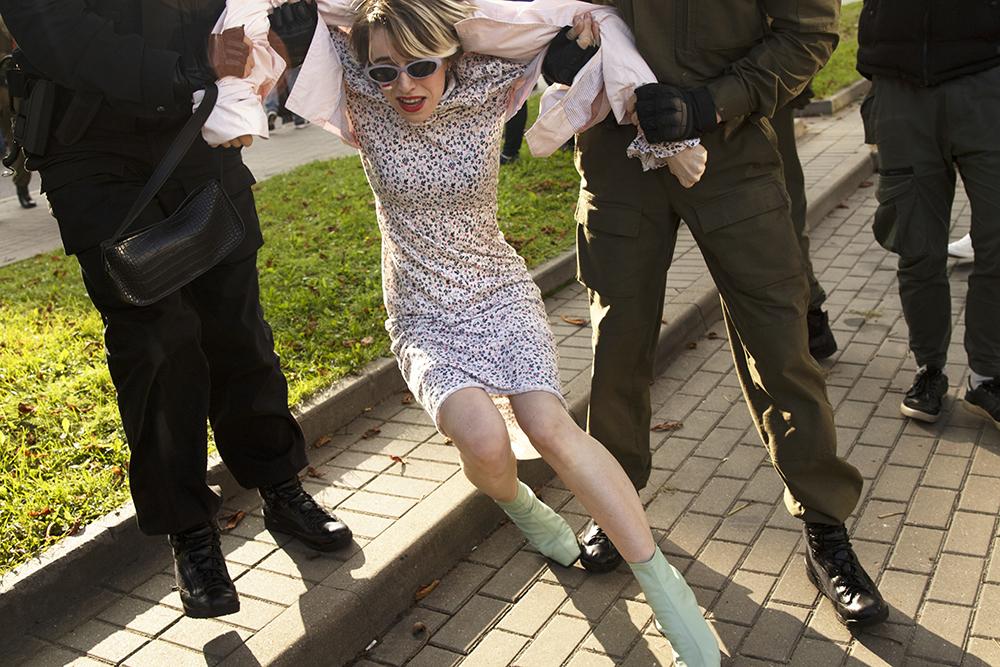 Eine junge Frau wird in einem Polizeifahrzeug abgeführt. Minsk, August 2020.