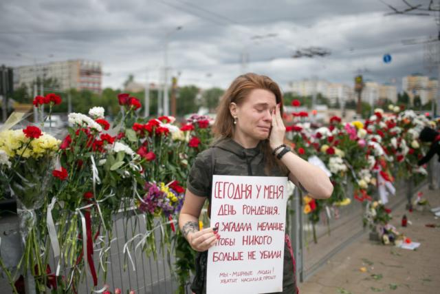 """Eine junge Frau weint in der Nähe des beliebten Denkmals zu Ehren des von der Polizei ermordeten Demonstranten Aleksandr Taraikovsky. Auf ihrem Plakat steht: """"Heute ist mein Geburtstag. Ich wünsche, dass sie niemanden mehr töten. Wir sind friedliche Menschen! Keine Gewalt mehr, ich bitte Sie"""". Minsk, August 2020."""