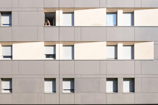 Une étudiante confinée dans une résidence universitaire de Poitiers prend l'air depuis sa fenêtre. De nombreux appartements semblent vides, les étudiants étant retournés dans leurs familles.